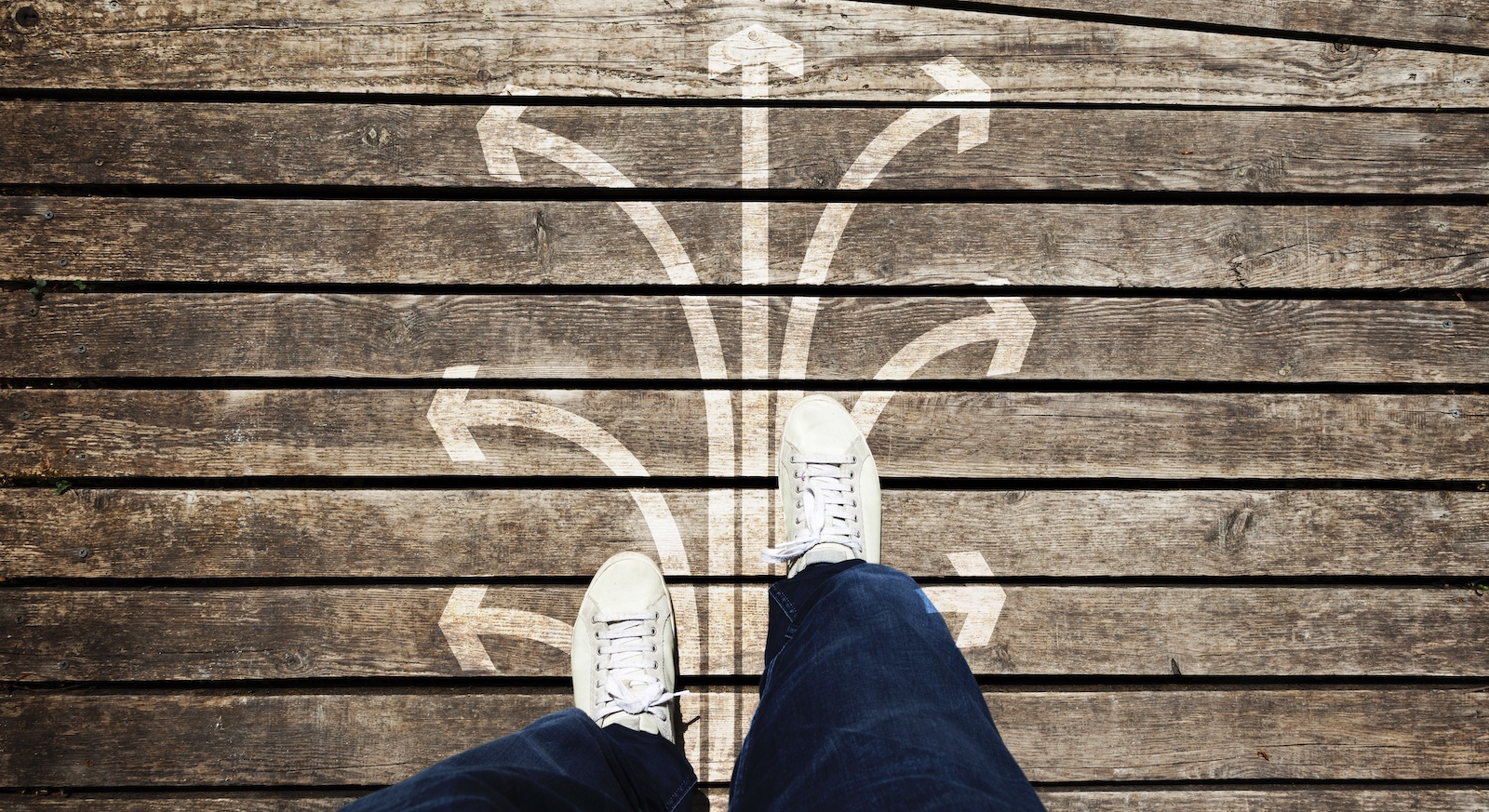 Man looking down at his shoes and arrows drawn on floor pointing in different directions